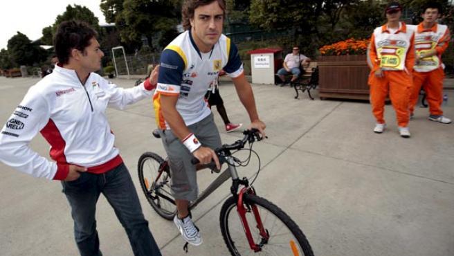 Fernando Alonso monta en una bicicleta por el Circuito Internacional de Shangai.