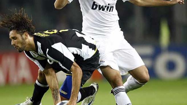 El madridista Pepe presiona al jugador del Juventus Amauri.