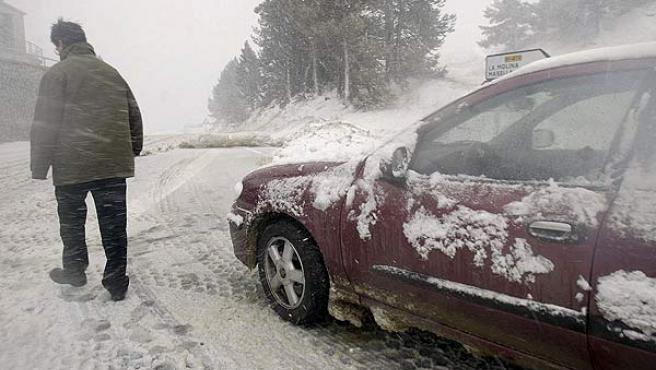 Un hombre camina sobre la nieve esta tarde en la Collada de Toses donde han caído las primeras nevadas de la temporada en el Pirineo gerundense.