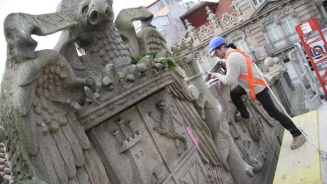 Un operario desmonta un escudo franquista en la Alcaldía de Vigo. (LAURA GONZÁLEZ)