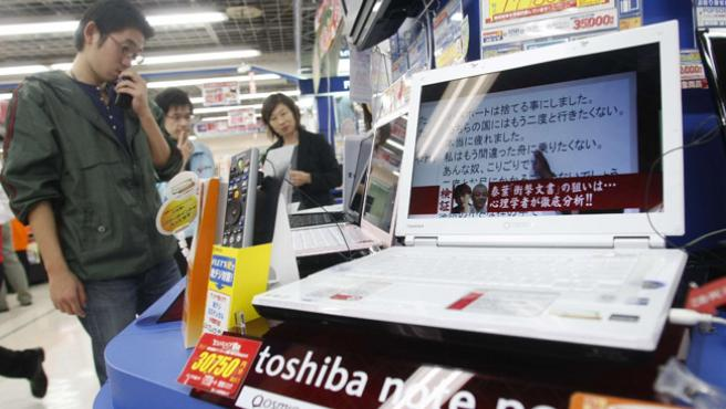 Un consumidor japonés en una tienda viendo portátiles.