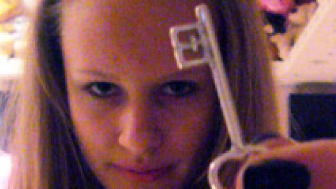 Una joven muestra una llave a la cámara.