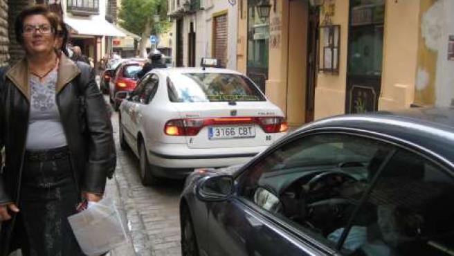 Peatones y vehículos comparten una calle muy estrecha.
