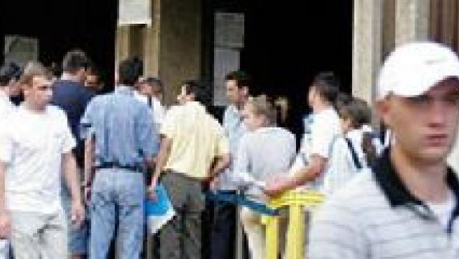 Inmigrantes rumanos hacen cola en una comsiaría madrileña para obtener el DNI