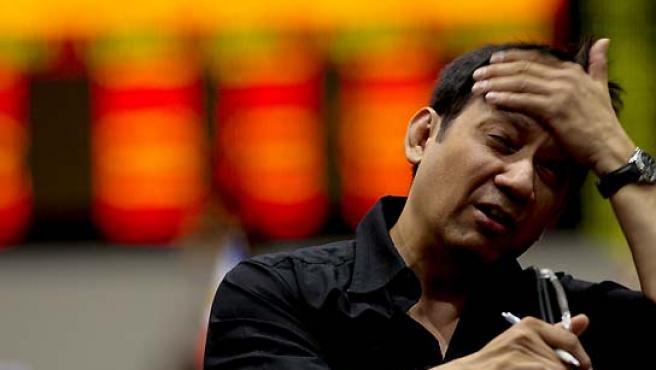 Un accionista reacciona al observar los índices de la Bolsa de Filipinas en el distrito financiero de Makati. (Akira Liwang / EFE).
