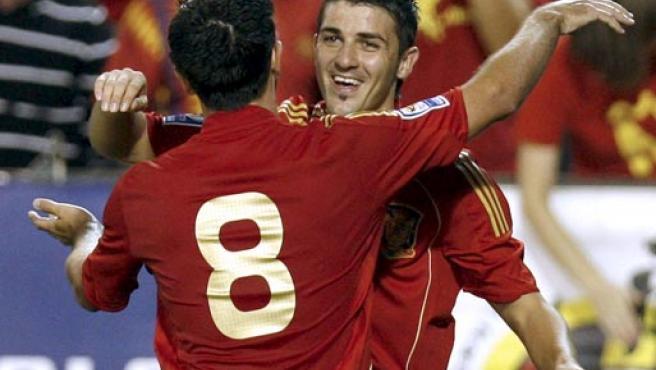 Villa y Xavi se abrazan tras el gol del asturiano. (EFE)