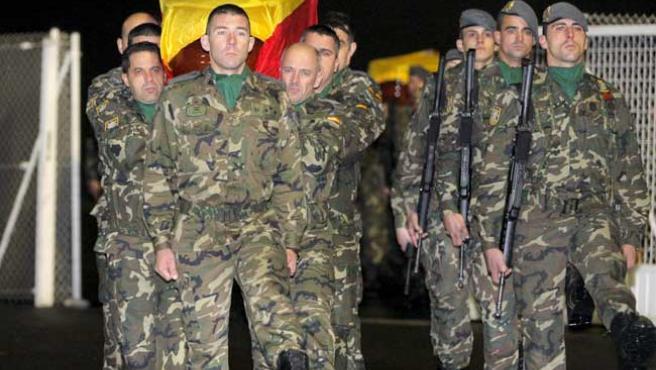Los féretros con los restos de Rubén Alonso Ríos y Juan Andrés Suárez García son portados a hombros por sus compañeros de la Brigada Ligera Aerotransportable, en el aeropuerto de Lavacolla (Lavandeira Jr / EFE)