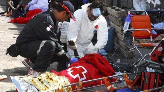Efectivos de emergencias atienden a una de las personas que llegaron el lunes en un cayuco hasta el puerto de La Restinga (EFE).
