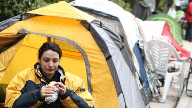 Roxana, de 30 años, tomando un bocadillo en la cola. (FOTO: J. PARÍS)