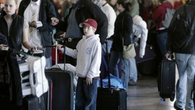 Los viajeros esperan a facturar sus equipajes.