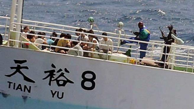 Dos piratas somalíes amenazan con sus armas a los tripulantes del barco pesquero chino 'Tian Yu 8', secuestrado en el Índico. (EFE)