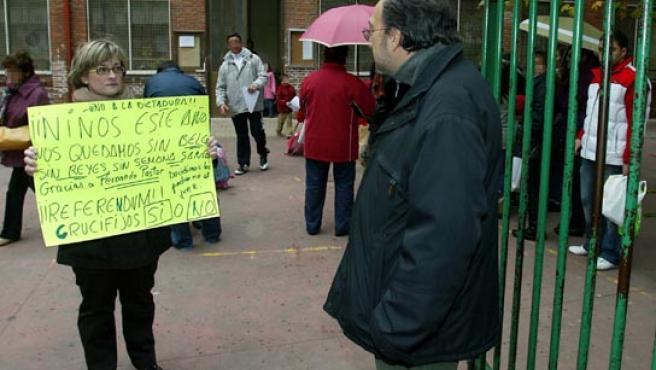 Una madre muestra una cartulina de rechazado a la sentencia ante Fernando Pastor.