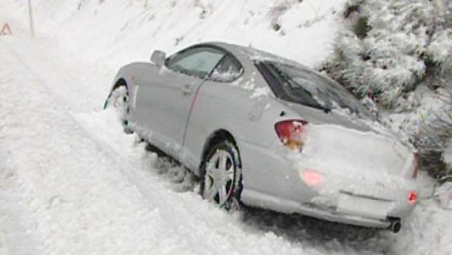 Un coche se queda en la cuneta a causa de la nieve en el puerto de Menga.