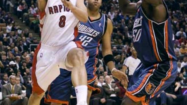 El extremeño de los Toronto Raptors Jose Calderón entra a acanasta ante Sean May (Centro) y Emeka Okafor (derecha), de los Bobcats.