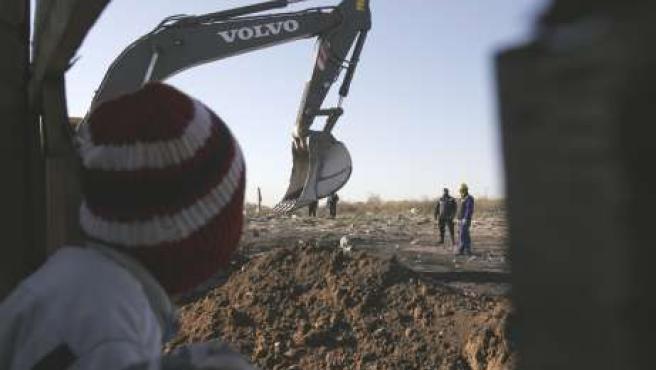 Un niño, mirando una excavadora al fondo