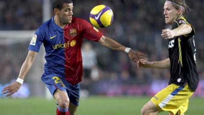 Dani Alves, lateral del Barcelona, controla el balón ante Eugen Polanski, mediocentro del Getafe.