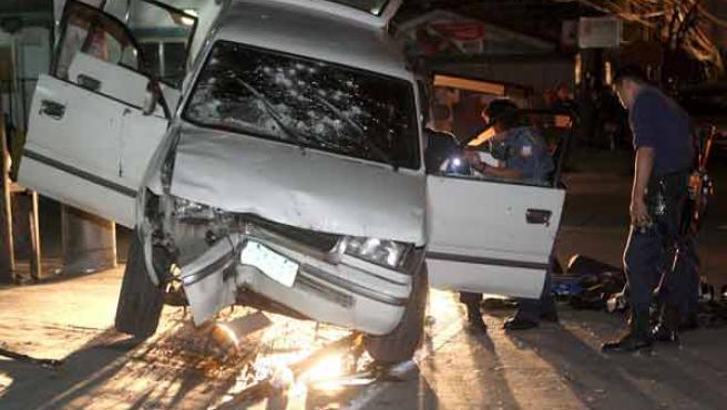 Un policía examina el coche que conducían uno de los grupos de atracadores. EFE