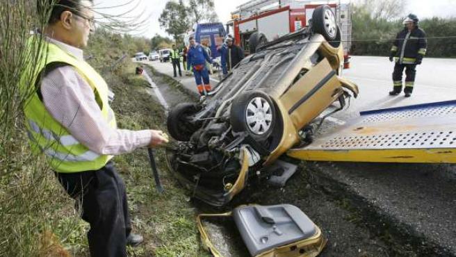Bomberos y Guardia Civil retiran el vehículo en el que falleció una joven de 24 años durante este puente en Pontevedra. EFE / SXENICK