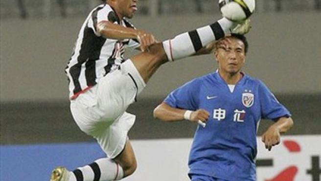 Jonathan Zebina, del Juventus (izq) lucha por un balón con Mao Jianqing, del Shanghai Shenhua.
