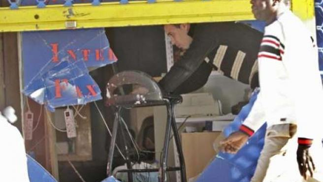 Un africano pasa frente a uno de los negocios de magrebíes atacados durante los disturbios. EFE