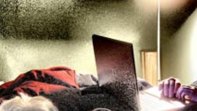 Una joven con el ordenador en la cama.