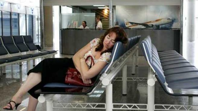 Imagen de archivo que muestra a una pasajera de Iberia esperando su vuelo en el aeropuerto. (REUTERS)