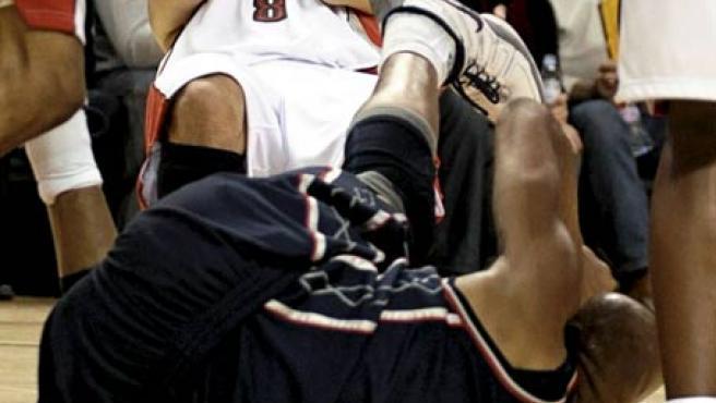 José Calderón (atrás) se toca la nariz tras chocar con Vince Carter, de los Nets de Nueva Jersey.