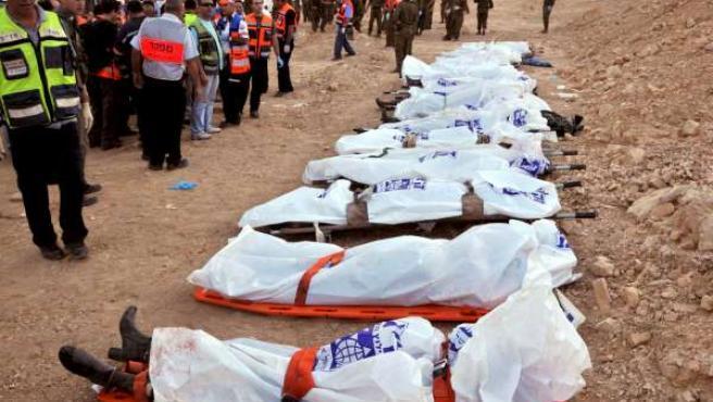 Algunos de los cadáveres permanecen cubiertos sobre camillas al borde de una colina por la que cayó el autobús (EFE).