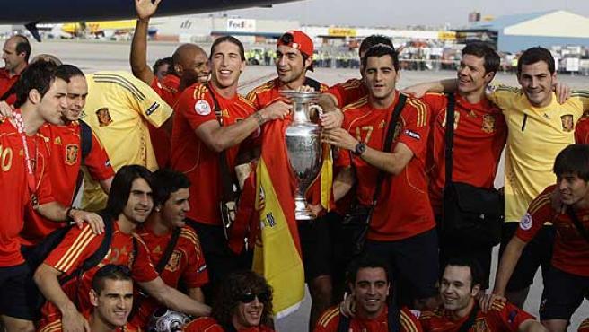 Los jugadores de la selección española posan con el trofeo de la Eurocopa en el aeropuerto de Barajas.