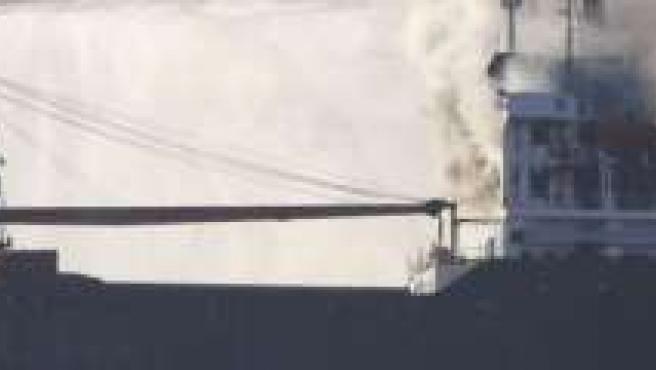 """Varias embarcaciones de Salvamento Marítimo arrojan agua hoy sobre el mercante """"Doxa"""", de bandera chipriota, que sufrió un incendio esta madrugada cuando se encontraba fondeado en la ría de Arousa."""