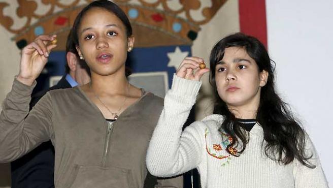 Rosmery y Tamara durante el último ensayo que han realizado los niños del colegio de San Ildefonso. (José Huesca / EFE).