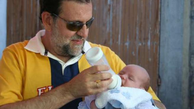 Mariano Rajoy dando el biberón a su bebé. (ARCHIVO)