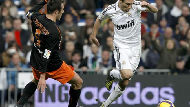 El centrocampista del Madrid Robben (d) avanza con el balón ante la oposición del defensa del Valencia Marchena (i). (EFE)
