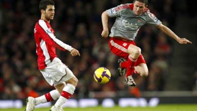 Cesc Fábregas, centrocampista del Arsenal, y Robbie Keane, delantero del Liverpool, luchan por un balón.