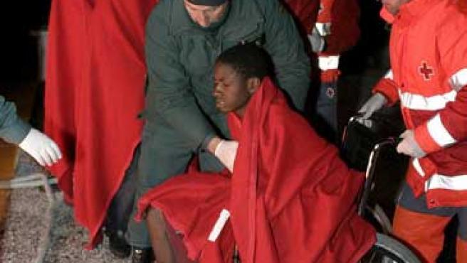 Algunos de los 37 inmigrantes, ayudados por la Guardia Civil y la Cruz Roja, en el puerto granadino de Motril (PAQUET / EFE)
