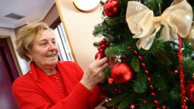 Asunción (75 años), colocando las bolas del árbol