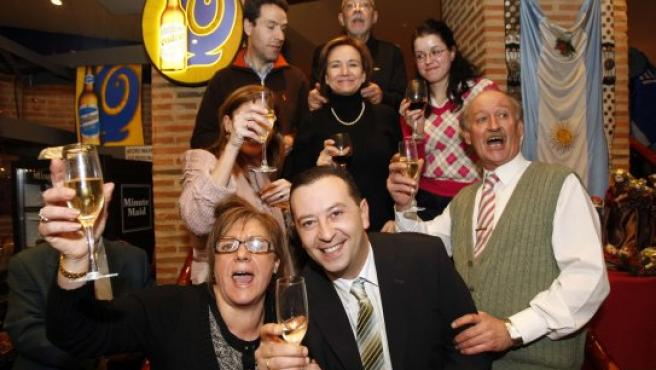 Cuatro trabajadores de Wolters Kluwer (abajo) junto a tres miembros de la administración de lotería número 22, que dio un quinto premio, y el dueño del Restaurante Papa y Tango.