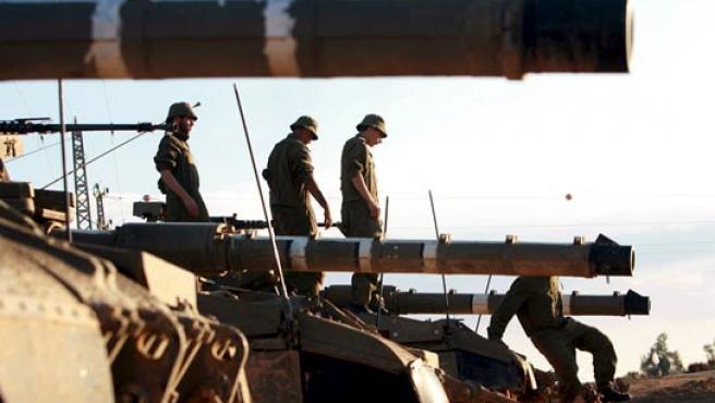 Soldados israelíes realizan labores de mantenimiento en tanques Merkavás en una base en la frontera con la franja de Gaza. (EFE)