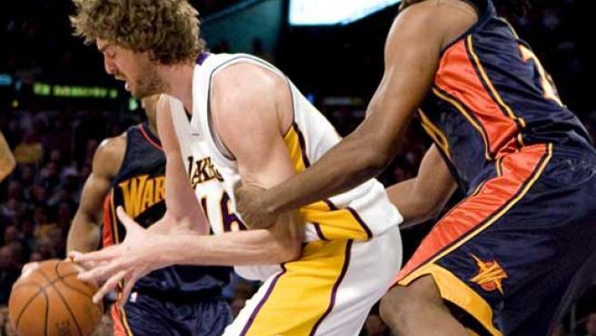 Pau Gasol (izq.), de los Lakers de Los Ángeles, domina el balón ante Ronny Turiaf, de los Warriors de Golden State.