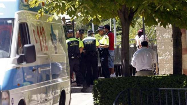 Agentes de la Policía en la puerta del parque Juan de Austria tras conocerse el fallecimiento de un niño.
