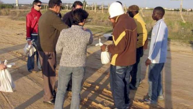 Patrocinio Mora contó con la ayuda de voluntarios, políticos y autoridades locales para repartir la comida. EFE/FERMÍN CABANILLAS.