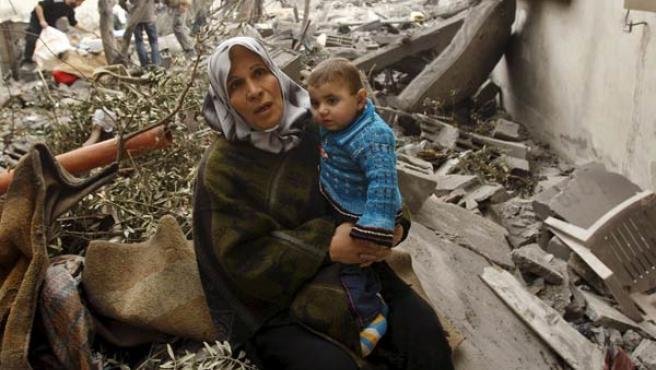 Una mujer palestina, con un niño, sentados sobre las ruinas de su casa (AGENCIAS).