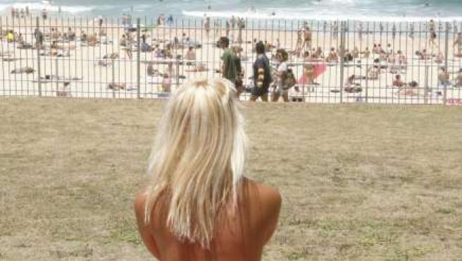 Una joven australiana toma el sol en topless. (REUTERS)