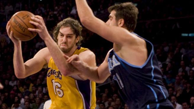 El jugador Pau Gasol (i) de los Los Ángeles Lakers intenta un lanzamiento ante la marca de Mehmet Okur de los Jazz de Utah. (EFE)