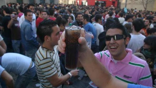 Jóvenes consumiendo alcohol en la calle durante un 'botellón'.