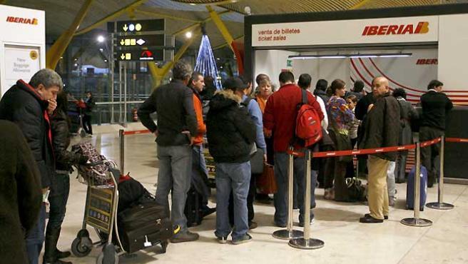 Varios viajeros hacen cola frente a la oficina de Iberia en la terminal 4 del aeropuerto de Barajas (Madrid). (EFE).