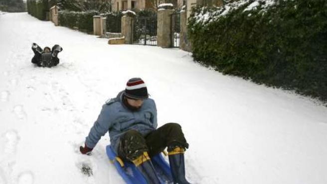 Dos jóvenes se deslizan con trineos por una calle de Prades (Tarragona) tras la nevada caída en las últimas horas. EFE/J.S