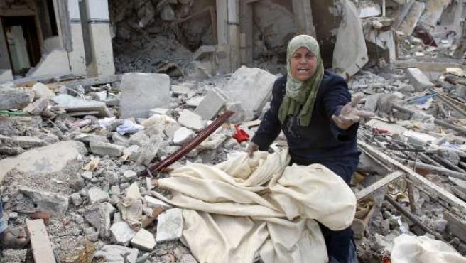 Una mujer palestina busca alguna de sus pertenencias entre los restos de su casa bombardeada, en Rafah (REUTERS).