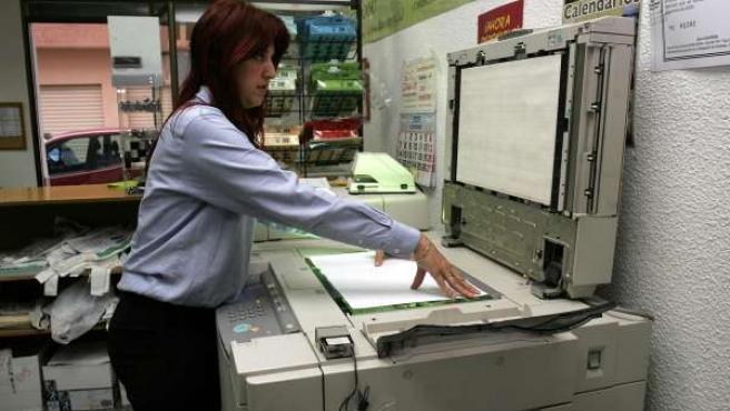 Una empleada de reprografía utilizando una fotocopiadora.