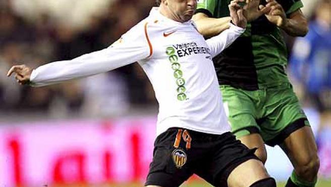 El valencianista Pablo Hernández dispara ante la presión de Serrano, del Racing.